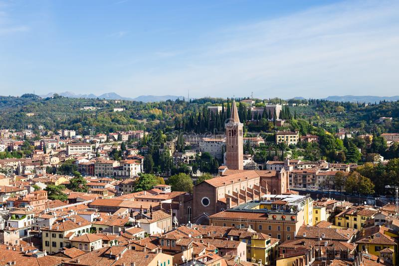 Cityscape of Verona with orange rooftops and green trees in sunny day. Aerial view of Verona city with St. Peter mountain and high tower, blue sky on background royalty free stock images
