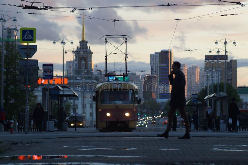 cityscape Vicolo, pozze, nuvole, tram, automobili, fari immagine stock libera da diritti