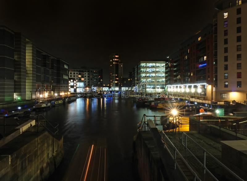 Cityscape view of clarence dock in leeds at night showing the lock gates and water surrounded by buildings royalty free stock images