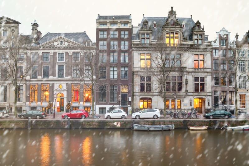 Cityscape - vintersikt av husen med festliga garneringar och stadskanalen med fartyg, stad av Amsterdam arkivfoto
