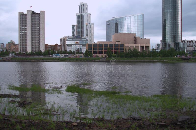 cityscape W pobliskim planie jest skalisty bank rzeka, trawa w wodzie fotografia royalty free