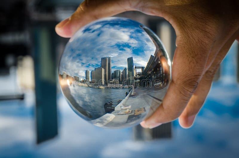 Cityscapefotografi i en klar glass kristallkula med dramatisk molnhimmel royaltyfria foton