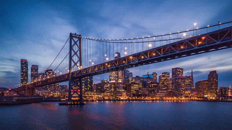 Cityscapesikt av San Francisco och fjärdbron på natten fotografering för bildbyråer