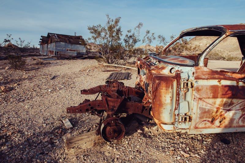 Ciudad abandonada en el desierto con los coches oxidados y las casas destruidas imagen de archivo
