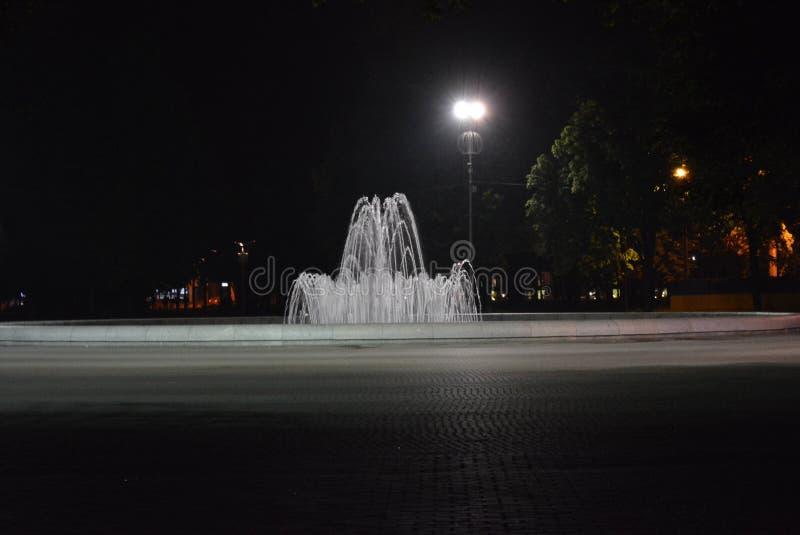 Ciudad agradable de la noche, una fuente en el centro del parque rodeado por las linternas imagen de archivo libre de regalías