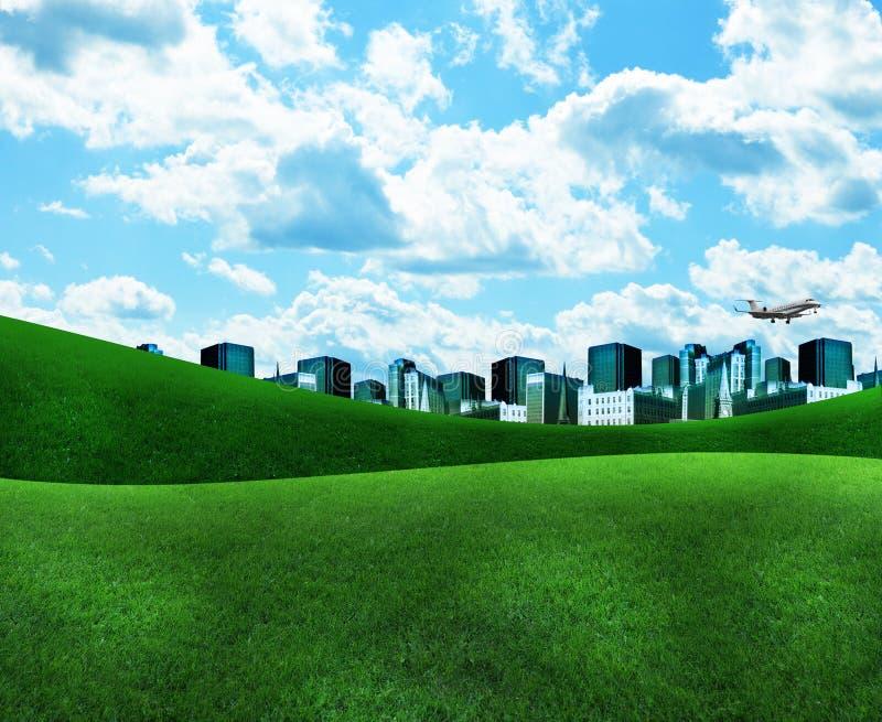 Ciudad azul con la hierba verde y las nubes imagen de archivo
