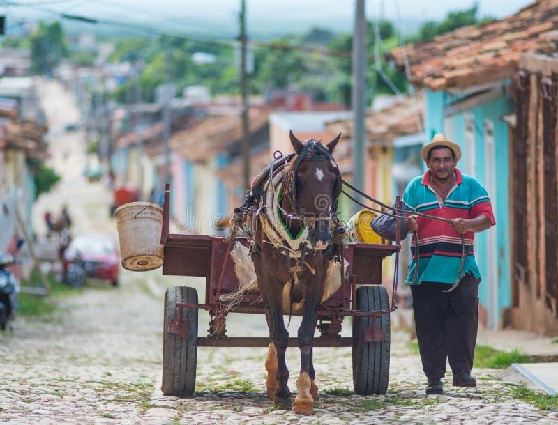 Ciudad colonial colorida de la tradición con el carro clásico, granjero, calle del guijarro en Trinidad, Cuba, América fotografía de archivo libre de regalías