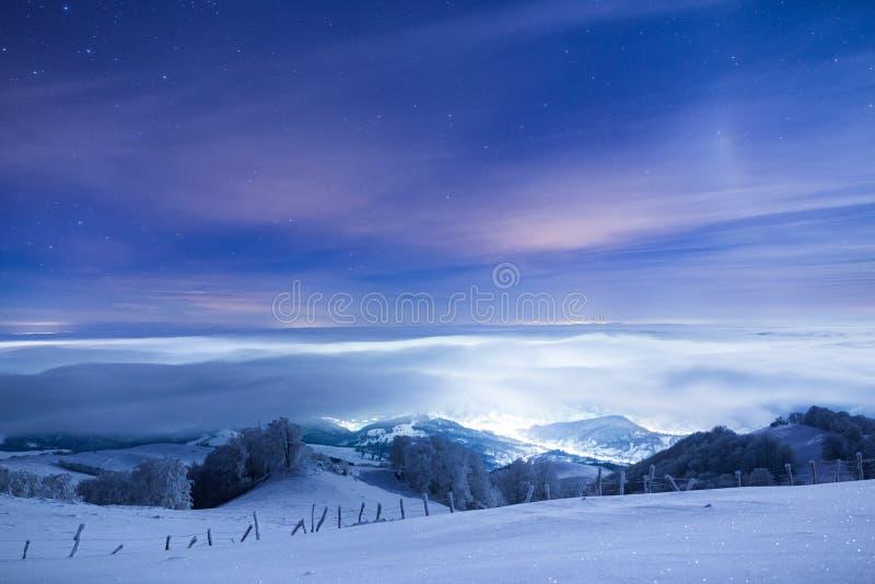 Ciudad congelada cubierta en niebla debajo de un cielo llenado de las estrellas fotografía de archivo libre de regalías