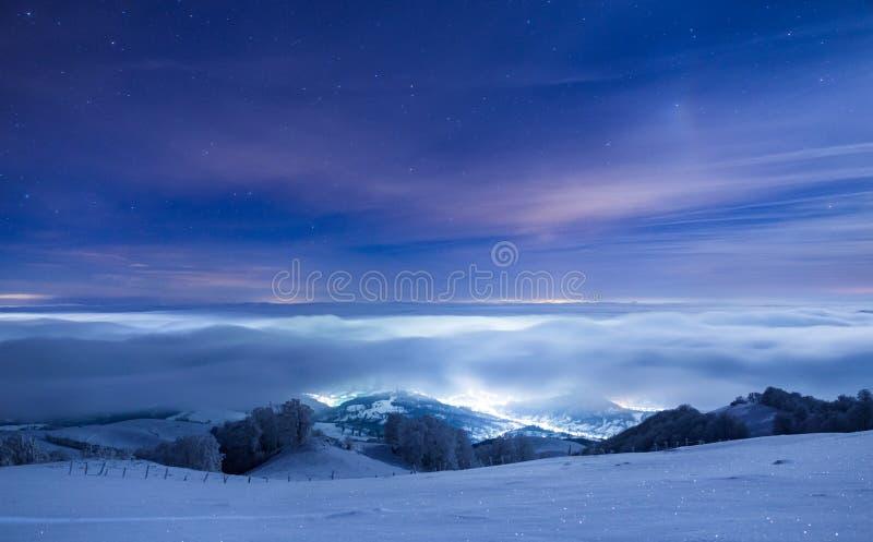 Ciudad congelada cubierta en niebla debajo de un cielo llenado de las estrellas foto de archivo