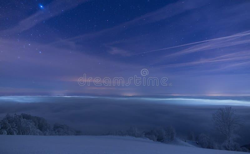 Ciudad congelada cubierta en niebla debajo de un cielo llenado de las estrellas fotografía de archivo
