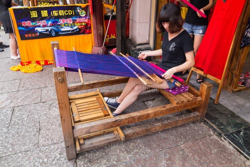 Ciudad de Huangshan Tunxi, China - circa septiembre de 2015: La muchacha teje la materia textil usando el dispositivo tradicional fotografía de archivo libre de regalías