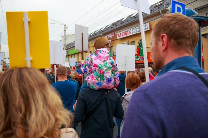 Ciudad de Kaluga, Rusia - mayo de 2019: el forraje-casquillo que lleva de la ni?a asienta en hombros de su padre y participa en d fotografía de archivo