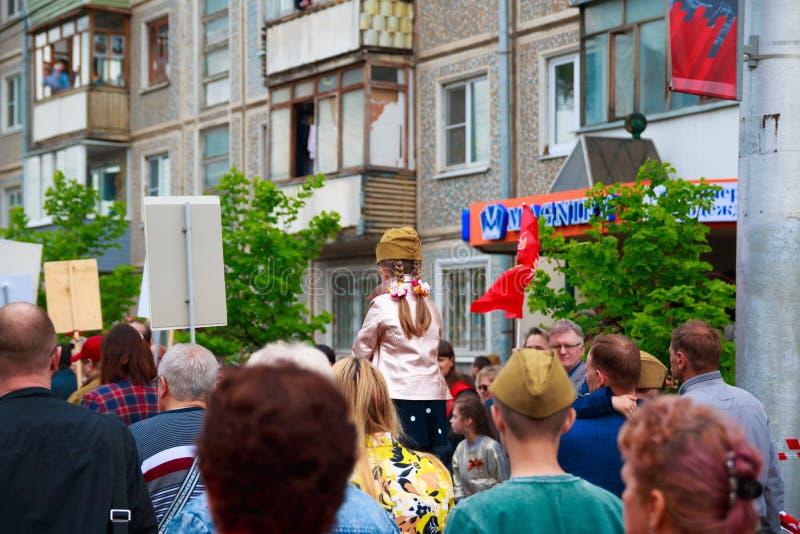 Ciudad de Kaluga, Rusia - mayo de 2019: el forraje-casquillo que lleva de la ni?a asienta en hombros de su padre y participa en d foto de archivo libre de regalías