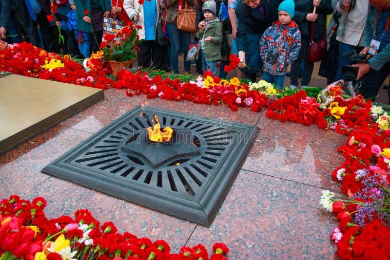 Ciudad de Kaluga, Rusia - mayo de 2019: la gente pone las flores a la victoria dedicada del fuego eterno en la gran guerra patri? imagen de archivo libre de regalías