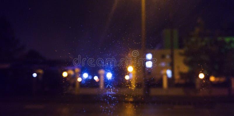 Ciudad de la noche, luces de neón, fondo borroso del bokeh, gotas de agua Opinión de la noche fotos de archivo libres de regalías