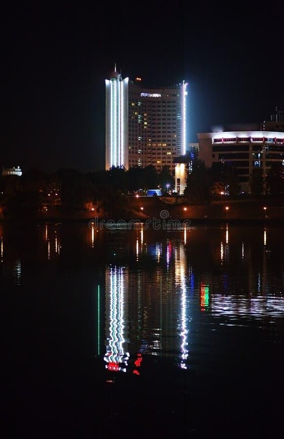Ciudad de la noche por el río Hermosa vista de la metrópoli para el fondo, Bielorrusia, Minsk, calle de Nemiga foto de archivo