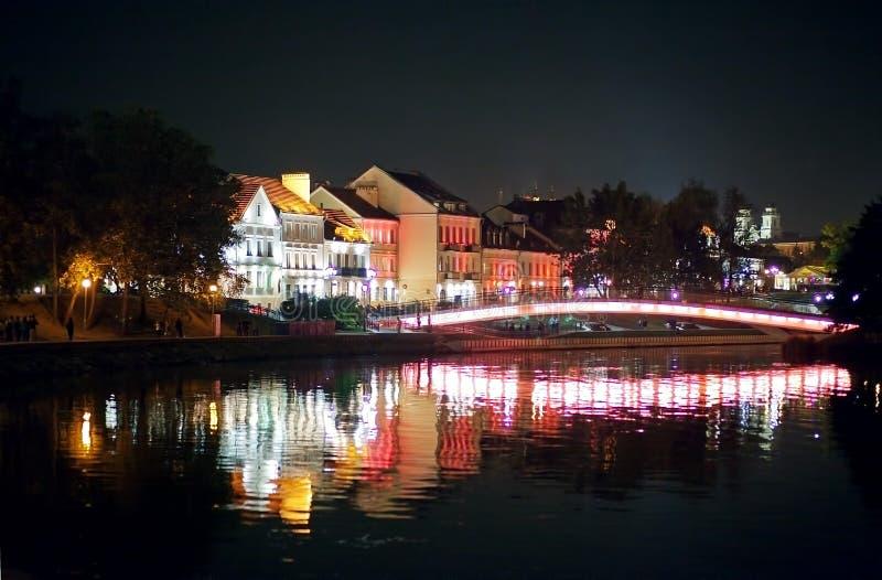Ciudad de la noche por el río Hermosa vista de la metrópoli para el fondo, Bielorrusia, Minsk, calle de Nemiga imagenes de archivo