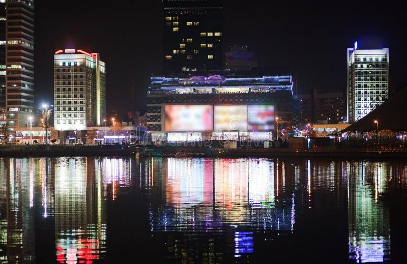 Ciudad de la noche por el río Hermosa vista de la metrópoli para el fondo, Bielorrusia, Minsk, calle de Nemiga foto de archivo libre de regalías