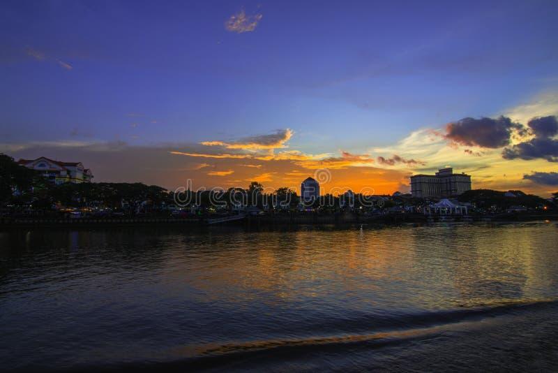 Ciudad de la orilla durante puesta del sol imagenes de archivo