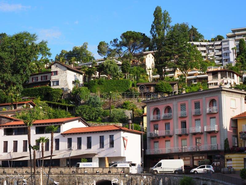 Ciudad del viaje de Ascona con la opinión escénica sobre casas coloridas en cuesta del paisaje alpino de la cordillera en Suiza fotos de archivo