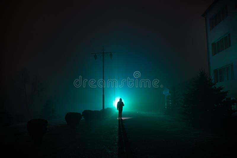 Ciudad en la noche en niebla densa Luces surrealistas del paisaje místico con el hombre espeluznante La silueta del hombre que ca fotografía de archivo