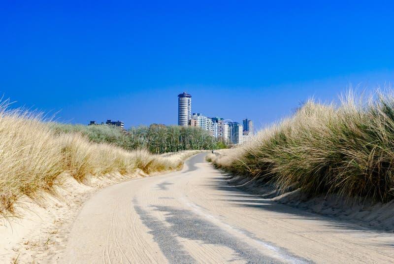 Ciudad futurista que asoma en y de un camino vacío, que corre a través de las dunas Verano Vacaciones Camino al desconocido Camin fotos de archivo libres de regalías