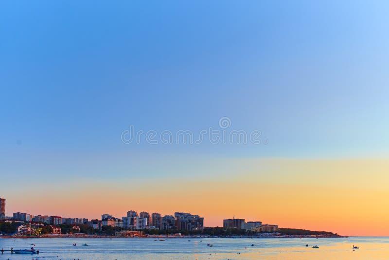 Ciudad grande por el mar en la puesta del sol foto de archivo