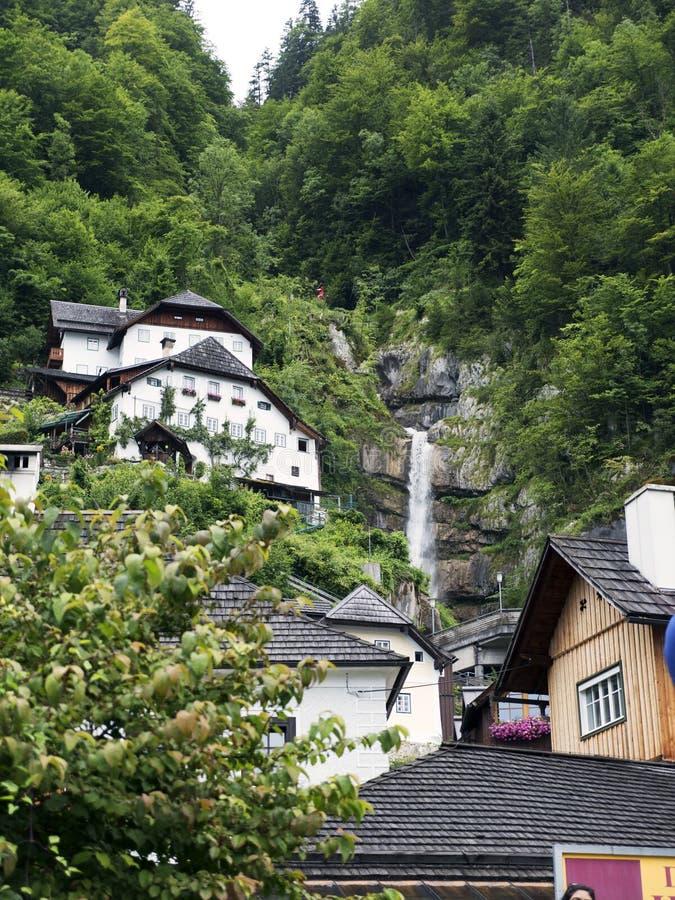 Ciudad Hallstatt con la cascada de la montaña Macizo alpino, barranco hermoso en Austria imagen de archivo libre de regalías