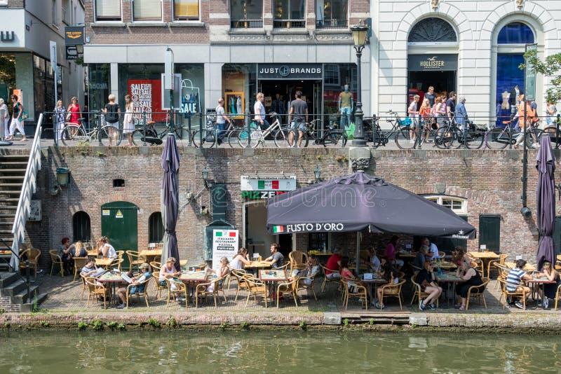 Ciudad holandesa Utrecht con la gente que hace compras y terraza a lo largo del canal foto de archivo