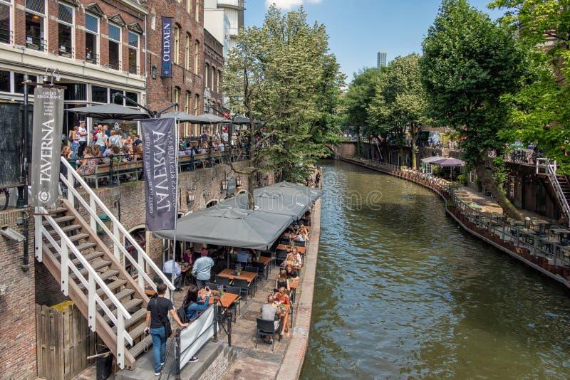 Ciudad holandesa Utrecht con la gente y las terrazas que hacen compras a lo largo del canal imagen de archivo