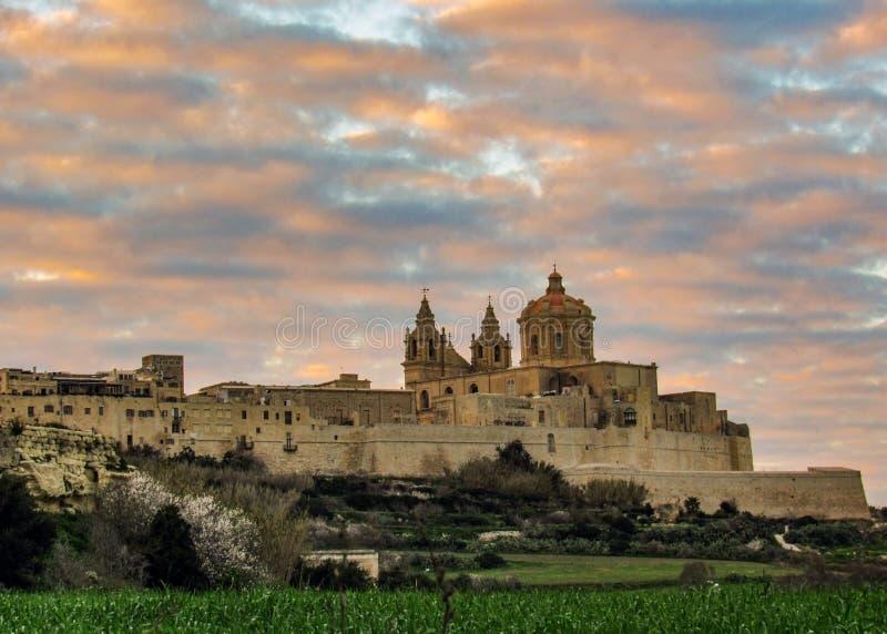 Ciudad medieval fortificada de Mdina Rabat de la ciudad incluida en bastiones con el cielo épico de la puesta del sol, situado en foto de archivo libre de regalías