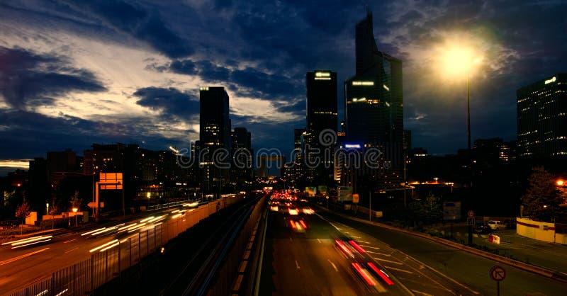 Ciudad Puesta del sol, nubes rotas contra el cielo brillante, luces de calles fotografía de archivo libre de regalías