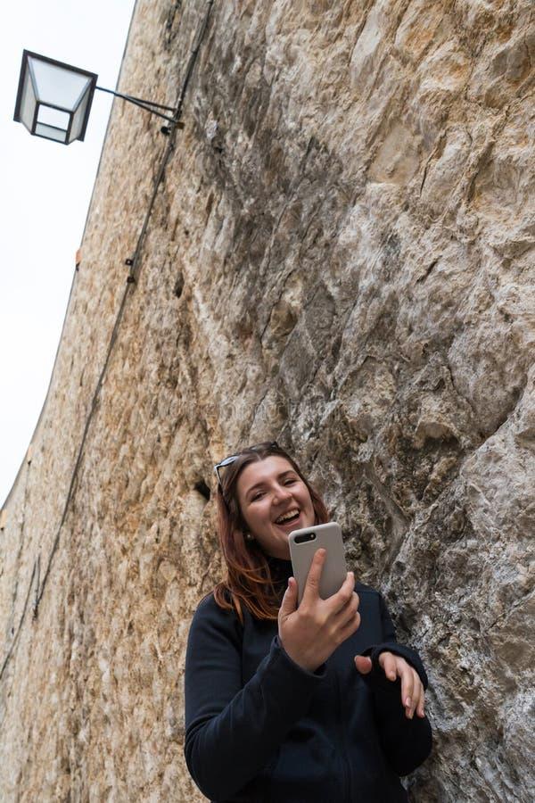Ciudad que visita de la mujer turística joven hermosa que hace turismo en la pared de piedra, sosteniendo el smartphone que toma  fotografía de archivo libre de regalías