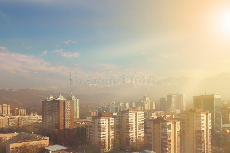 Ciudad soleada en el pie de las montañas nevosas fotografía de archivo