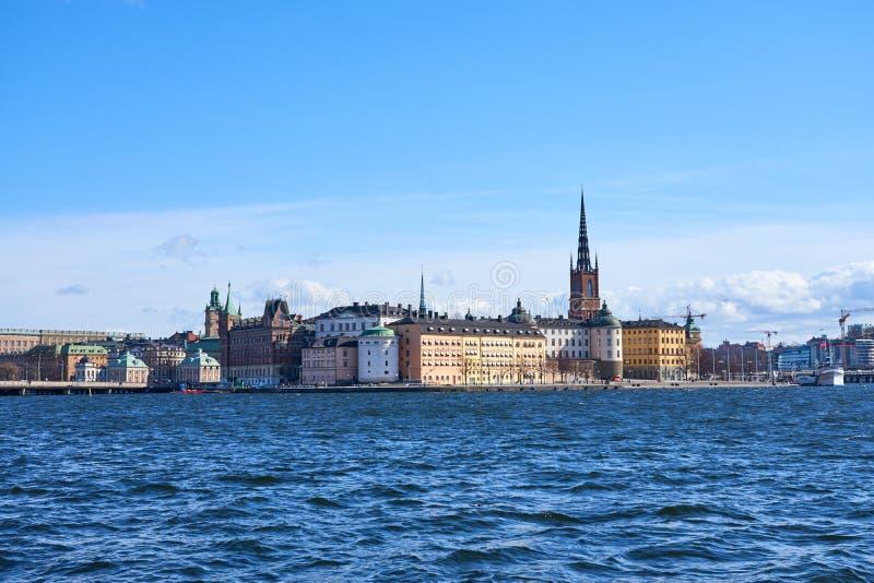 Ciudad vieja de Estocolmo con las ondas en el agua azul debajo del cielo nublado azul fotografía de archivo