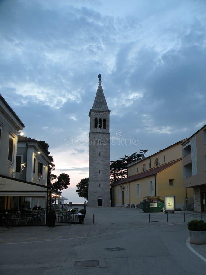 Ciudad vieja de Istrian de Novigrad, Croacia Una iglesia hermosa con un alto campanario elegante, callejones de piedra y una casa imagen de archivo libre de regalías