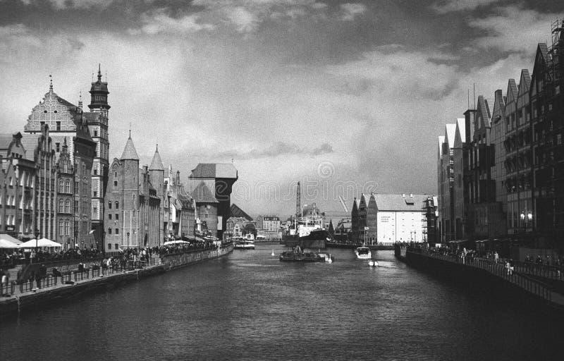 Ciudad vieja en Gdansk en la exploración negativa blanco y negro en la puesta del sol cerca de un lago imagen de archivo