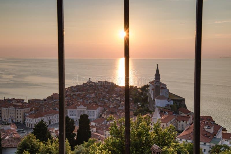 Ciudad vieja hermosa de Piran en la costa costa del mar adriático en la puesta del sol, visión a través de barras, Eslovenia fotos de archivo libres de regalías
