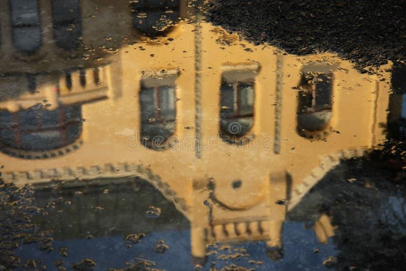 Ciudad vieja que refleja en un charco después de lluvia fotografía de archivo