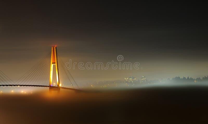 Ciudad y puente hermosos de la cubierta de la niebla de la noche en un día de niebla imagenes de archivo