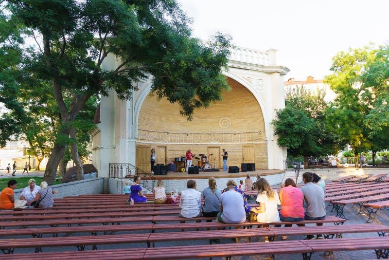 Ciudadanos y visitantes de la ciudad en los bancos en la plataforma de la etapa al aire libre que espera el concierto de la tarde imagen de archivo libre de regalías