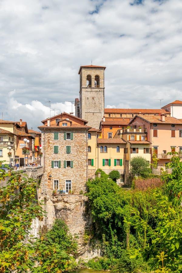 Cividale del Friuli, Italien: Sikt av det gamla centret med traditionell arkitektur Flod Natisone med genomskinligt royaltyfri fotografi