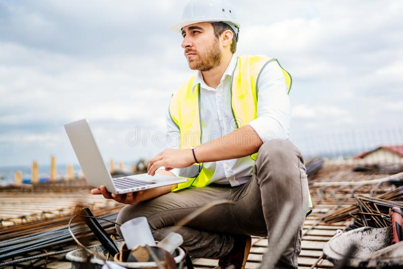 Civil construction engineer, working with laptop on construction site stock image