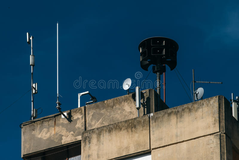 Civil defense siren on top of apartment building. Also known as air raid siren, provides emergency warning of approaching danger such as tornadoes stock photo