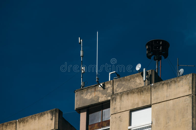 Civil defense siren on top of apartment building. Also known as air raid siren, provides emergency warning of approaching danger such as tornadoes royalty free stock photo