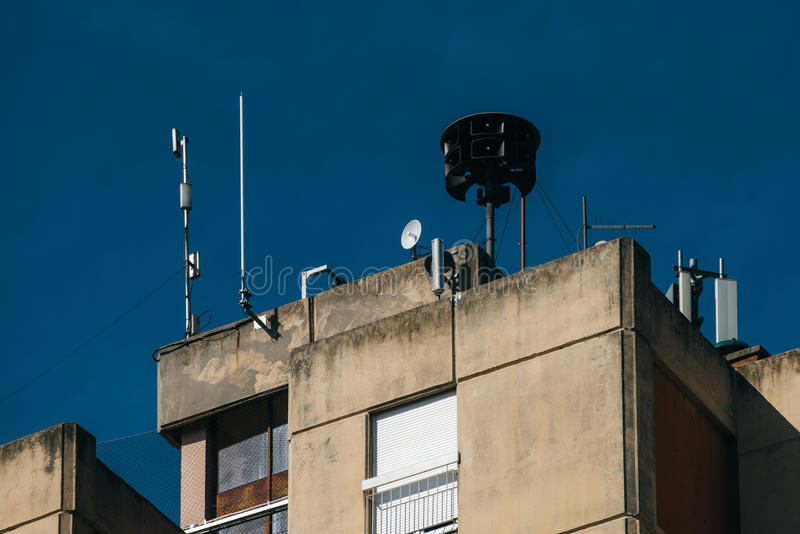 Civil defense siren on top of apartment building. Also known as air raid siren, provides emergency warning of approaching danger such as tornadoes stock image