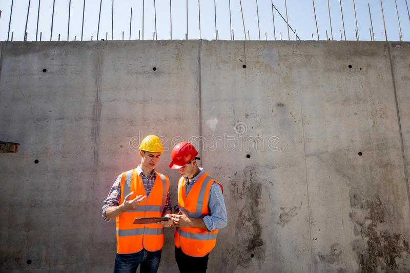 Civil engineer and architect dressed in orange work vests and helmets stand on a concrete wall background and use tablet stock image