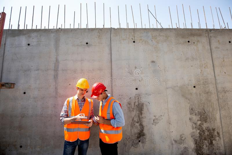 Civil engineer and architect dressed in orange work vests and helmets stand on a concrete wall background and use tablet stock photos