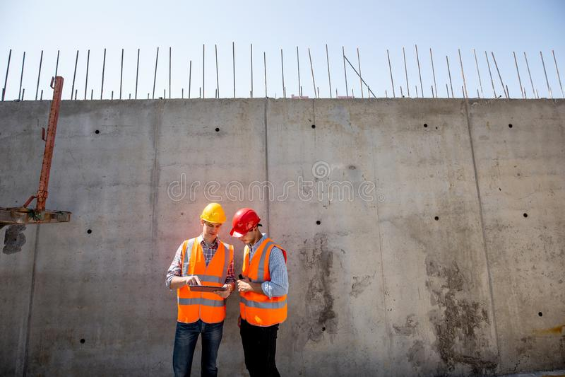 Civil engineer and architect dressed in orange work vests and helmets stand on a concrete wall background and use tablet stock images