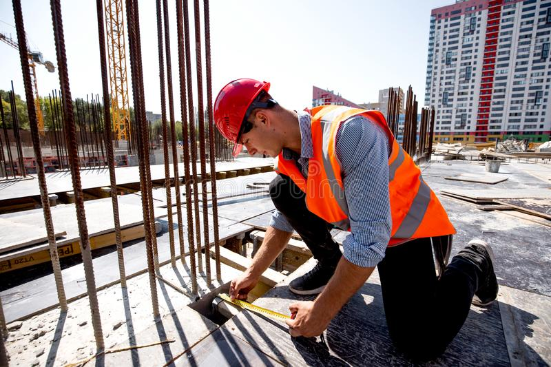 Civil engineer dressed in shirt, orange work vest and helmet measures the hole with a tape measure on the building site stock image